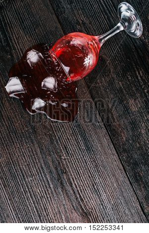 Wine glass with red liquid lying on the dark wood surface. Flat lay
