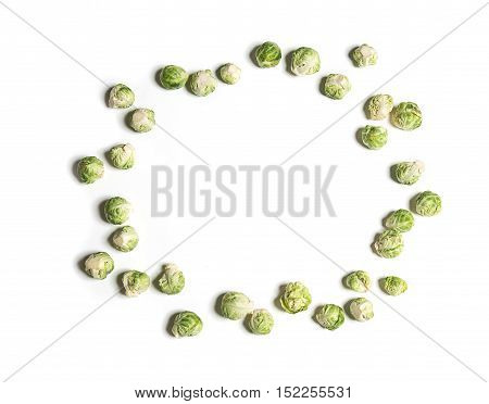 Baby brussels sprouts isolated on white as a frame top view. Copy space for text