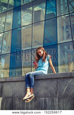 Outdoor shot of stylish girl holding a smartphone, wearing sunglasses against business center on a bright summer day