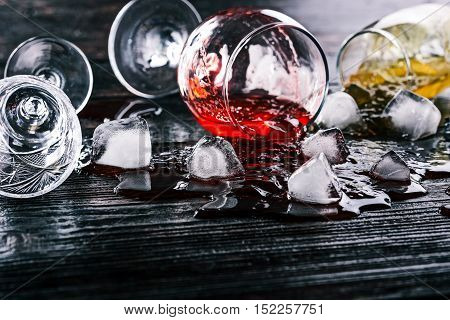 Wine glasses with colorful liquids and ice cubes lying on the dark wood surface. Close up. Selective focus