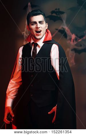 Young man dressed as vampire for Halloween party, on dark background