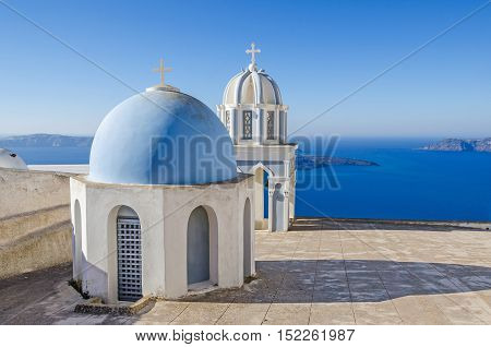 One of many typical chapels of Greek Orthodox Church on the greek island Santorini in Thira with Aegean Sea and the uninhabited island of Nea Kameni in the background.