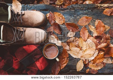 Two pairs of hiking boots on wooden bench on fallen autumn leaves in the forest, outdoor travel concept, top view