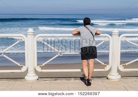 Short haired woman wearing miniskirt looking at the sea from the promenade