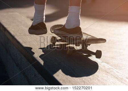 Foot on a skateboard. Skater riding outdoors. No fear and no doubt. Be young and live free.