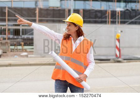 Single female construction engineer in vest pointing finger as if to show or direct attention toward a building project