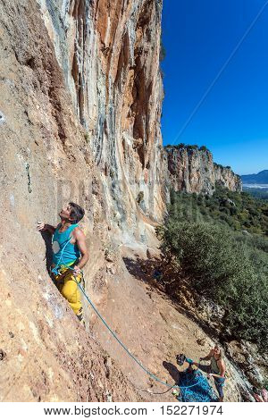Mature male extreme Climber moving up on red orange vertical high natural rocky Wall female Partner belaying him on rope blue clear Sky sunshine weather