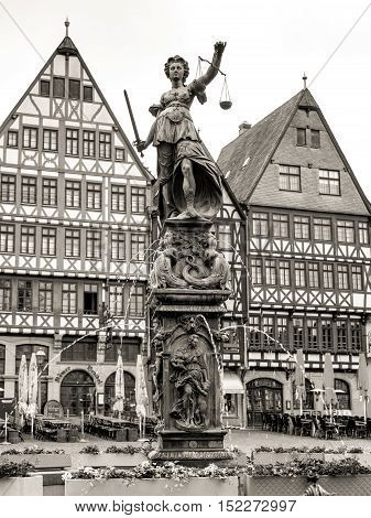 Frankfurt am Main, Germany - May 29, 2016: Old town square Romerberg with Justitia statue in Frankfurt Germany. Black and white photography sepia toned.