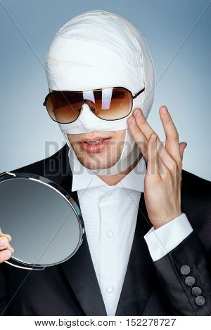 Glamorous man in sunglasses looking in the mirror touching his new face. Beauty victim with bandage on his face after facelift. Plastic Surgery concept.