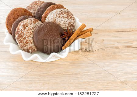 Variety of traditional German Gingerbreads in a white porcelain bowl isolated on brown wooden background.