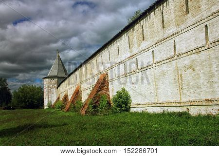 high white stone wall of the ancient Orthodox monastery with brick buttresses