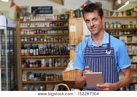 Portrait Of Man Working In Delicatessen Using Digital Tablet