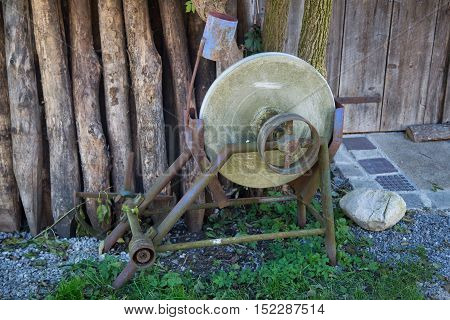 Old grindstone in front of wooden barn, antique