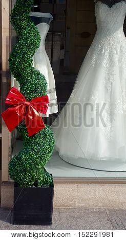 Big red bow and wedding dresses in a shop window