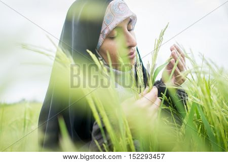 Beautiful happy Muslim woman in green field