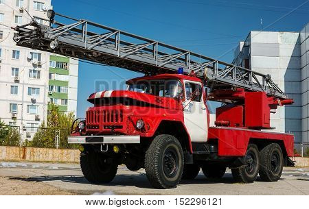 big red fire truck with a ladder close-up.