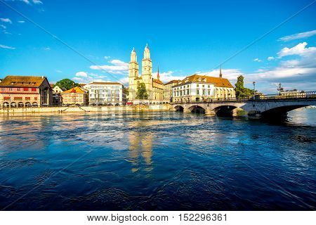 View on the riverside with beautiful buildings and Great Minster Church in Zurich city in Switzerland