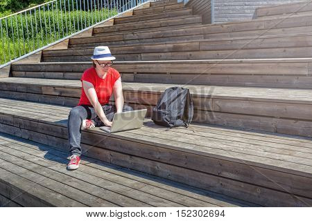 Girl with glasses lying on the wooden stairs and using laptop and typing