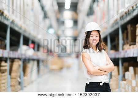 Beautiful young Asian engineer or technician smiling warehouse or factory blur background industry or logistic concept with copy space