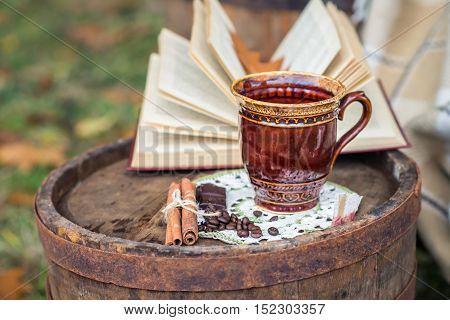still life with cinnamon sticks coffee beans and coffee cup on the old oak barrel in the garden autumn