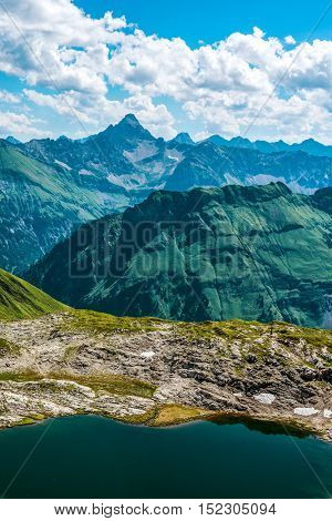 Striking view of ancient rugged mountain range with a sparse covering of grasses and having a pure pool of water on top