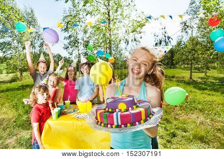 Happy birthday girl in party hat holding birthday cake, standing among her friends at the outdoor party