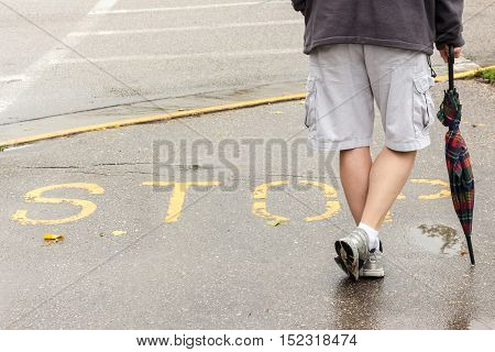 image of the bottom half of a man standing on wet pavement leaning on his umbrella with the word