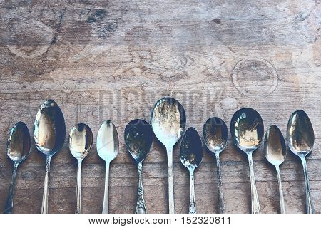 Over head flat lay view of a collection of tarnished silver spoons side by side on rustic table