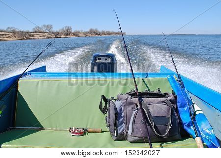 Feed motor boats. The boat leaves a trail on the water. Bag and fishing rods in the back seat