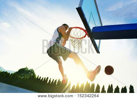 Street Basketball Player Performing Power Slum Dunk.