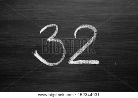 number thirty two enumeration written with a chalk on the blackboard