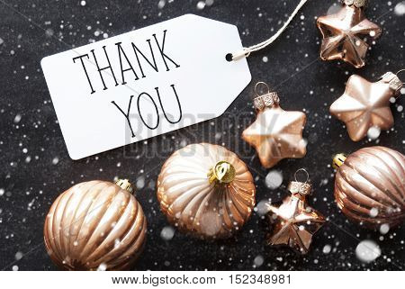 Label With English Text Thank You. Bronze Christmas Tree Balls On Black Paper Background With Snowflakes. Christmas Decoration Or Texture. Flat Lay View