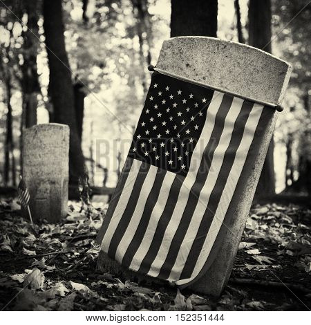 A 19th century headstone with an American flag surrounded by dry leaves and trees in a spooky forest. Film grain black and white filter applied.
