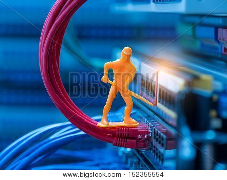 Miniature Technicians connecting network cable