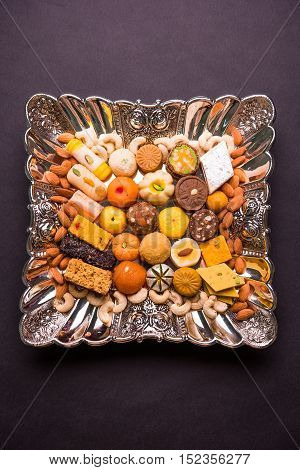 Mix Mithai or indian milk made sweets, favourite diwali, holi, dussehra, indian or pakistani wedding sweet food served in a square silver decorative plate