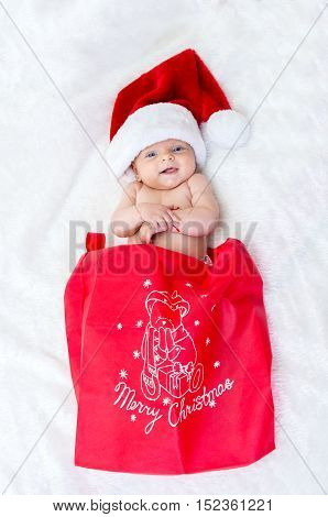 Cute Baby Girl On The Bed Wearing A Santa Hat For Christmas.