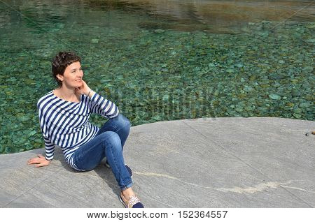 Thoughtful young brunette woman sitting on a rock against  clear Verzasca river background. Travel concept