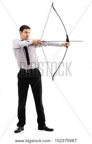Full length portrait of a young businessman aiming with a bow and arrow isolated on white background