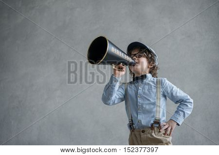 Little child with a megaphone in studio