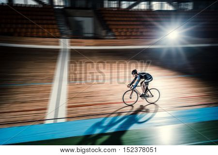 Athlete on a bicycle on velodrome