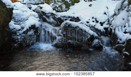 Detail stream with ice and snow on the rocks