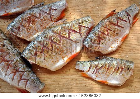 The process of preparation of river fish on a rustic kitchen. Peppered salted and incised chub and roach on the wooden surface.