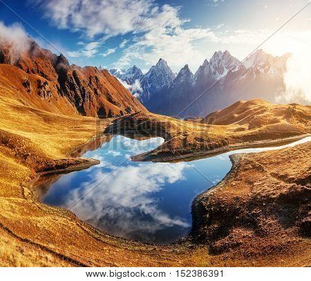 Fantastic lake Koruldi at the foot of Mt. Ushba. Dramatic scene. Location famous place Upper Svaneti, Mestia, Georgia, Europe. High Caucasus ridge. Warm toning, soft filter effect. Beauty world.