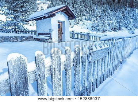 Frozen wooden fence and rustic chapel - Winter idyllic scenery with an old wooden fence covered by snow which surrounds a rustic alpine chapel in the Austrian Alps. Image taken in Ehrwald Austria.