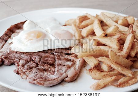 Gammon egg and chips served on a white plate - filter applied