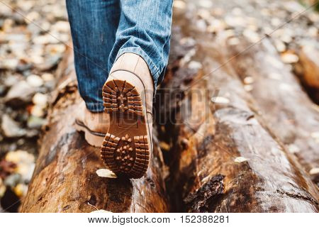 Hiker wearing boots walking across river in autumnal forest. Footwear on man's legs outdoor. Male seasonal shoes. Sole protector closeup.