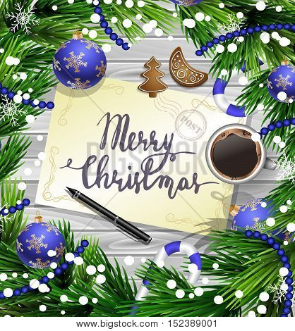 Christmas New Year design wooden background with christmas decorations candy canes snow and balls arranged in a frame with handwritten Merry CHristmas a cup of coffee gingerbread cookies and a pen in blue.