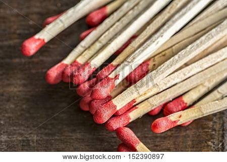 Closeup matchsticks with red heads on wooden background