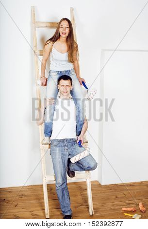 portrait of happy young new family doing repair in own flat, couple near ladder, lifestyle people concept smiling