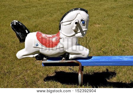 An old plastic horse serves as a seat on the end of a vintage teeter totter